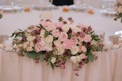 El ramo maravillosamente adornado de rosas adentro compone con las velas Imágenes de archivo libres de regalías