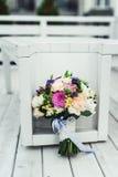 El ramo nupcial de diversas flores envolvió la cinta del cordón en un fondo blanco Foto de archivo