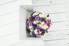 El ramo nupcial de diversas flores envolvió la cinta del cordón en un fondo blanco Foto de archivo libre de regalías