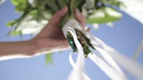 El ramo nupcial hermoso en manos de la novia joven se vistió en el vestido de boda blanco Ciérrese para arriba de manojo grande d almacen de metraje de vídeo