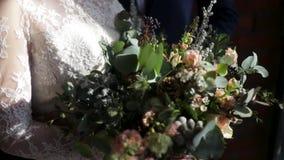 El ramo nupcial hermoso en manos de la novia joven se vistió en el vestido de boda blanco Mano de la novia que toca el ramo de la almacen de metraje de vídeo