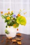 El ramo rústico brillante de marchitar florece en un florero de cerámica Imagen de archivo