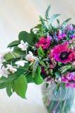 El ramo romántico hermoso de anémona y de orquídea rosadas florece en florero en el fondo blanco imagenes de archivo