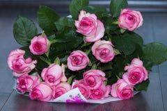 El ramo rosado de las rosas con agua cae en el piso Imagen de archivo libre de regalías
