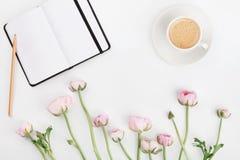 El ranúnculo hermoso de la primavera florece, cuaderno y taza de café vacíos en el escritorio blanco desde arriba Tarjeta de feli Imagen de archivo