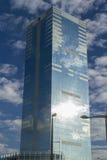 El rascacielos de cristal con el cielo azul y las nubes reflejó en ventanas Imagen de archivo libre de regalías