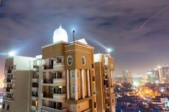 El rascacielos tiró contra el paisaje urbano del noida en noche nublada Foto de archivo