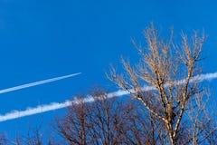 El rastro de la condensación destacó por el sol poniente detrás de un avión de pasajeros bimotor del turborreactor en el cielo de Fotografía de archivo