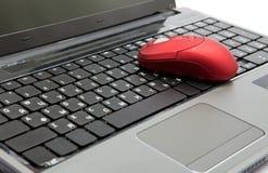 El ratón rojo del ordenador en el teclado negro Fotografía de archivo