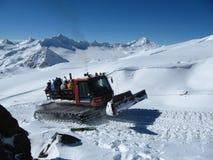 El ratrak de la montaña lleva snowboarders y a esquiadores en la alta cuesta de la montaña foto de archivo libre de regalías
