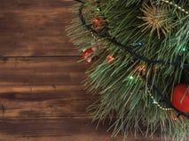 El árbol de navidad verde adornado con los juguetes y la guirnalda llevó luces en la picea festiva de la tabla de madera Foto de archivo libre de regalías
