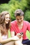 El reírse adolescente joven de los pares SMS Fotos de archivo libres de regalías