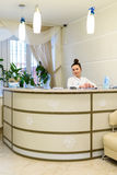 El recepcionista de la mujer en capa médica se coloca en el mostrador de recepción Imagen de archivo libre de regalías