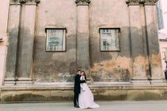 El recién casado romántico sonriente junta el abarcamiento delante de la pared vieja del castillo Fotografía de archivo