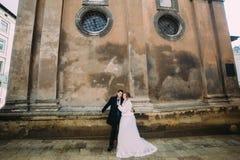 El recién casado romántico sonriente junta el abarcamiento delante de la pared vieja del castillo Imagenes de archivo