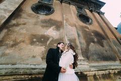 El recién casado romántico sonriente junta el abarcamiento delante de la pared vieja del castillo, opinión del primer de debajo Fotos de archivo