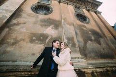 El recién casado romántico sonriente junta el abarcamiento delante de la pared vieja del castillo, opinión del primer de debajo Fotografía de archivo