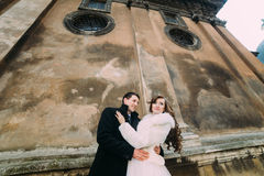 El recién casado romántico sonriente junta el abarcamiento delante de la pared vieja del castillo, opinión del primer de debajo Imagen de archivo