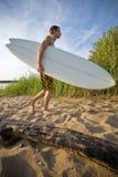 El recorrer en la playa y sostener una tabla hawaiana Imágenes de archivo libres de regalías