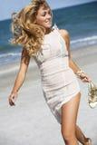 El recorrer rubio atractivo en la playa Foto de archivo