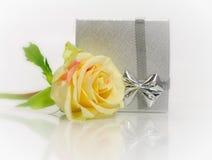 El rectángulo de regalo de plata con el pastel se levantó fotos de archivo