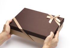 El rectángulo de regalo en las manos a sostenerse en un fondo blanco. Foto de archivo