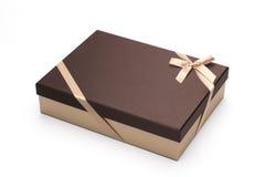 El rectángulo de regalo es envuelto para arriba por una cinta amarilla con un arqueamiento, aislado en blanco. Fotos de archivo