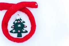 El recuerdo adornó el árbol de navidad en la nieve envuelta en una bufanda Fotos de archivo libres de regalías