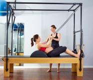 El reformador de los pilates de la mujer embarazada rueda para arriba ejercicio imagen de archivo