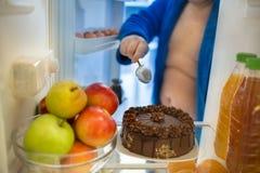 El refrigerador con la torta de chocolate de buen gusto agradable es prueba dura grande para foto de archivo libre de regalías