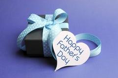 El regalo y el mensaje azules felices del tema del día de padres en corazón marcan con etiqueta Foto de archivo