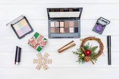 El regalo compone, los cosméticos y los ornamentos y los juguetes del Año Nuevo en el fondo de madera blanco imagenes de archivo
