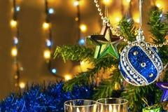 El regalo con dos velas y la Navidad juegan con las luces multicoloras en fondo Fotografía de archivo libre de regalías