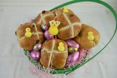 El regalo de la cesta de Pascua llenó de los huevos de chocolate y de los bollos cruzados calientes Imagen de archivo