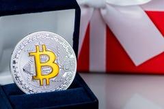 El regalo de la Navidad o el Año Nuevo con la cinta y el mejor bitcoin del regalo acuña en fondo ligero Investition de Cryptocurr Fotografía de archivo