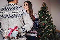 El regalo de la sorpresa de la tenencia del hombre detrás apoya para su mujer la Navidad e imágenes de archivo libres de regalías