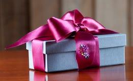 El regalo de vacaciones embaló en Grey Box con la cinta púrpura en W brillante Fotos de archivo
