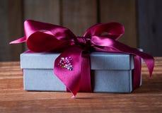 El regalo de vacaciones embaló en Grey Box con la cinta púrpura en W rústico Imagenes de archivo