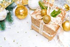 El regalo del Año Nuevo en una caja de oro, adornada con baronet, las ramas de árbol de navidad y los juguetes de la Navidad Imagen de archivo libre de regalías