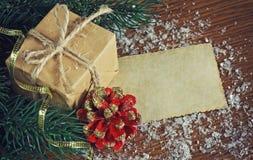 El regalo del Año Nuevo, los conos rojos, las ramas del abeto y etiqueta de papel Fotografía de archivo libre de regalías