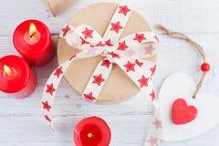 El regalo en la caja de Kraft con el rojo protagoniza la cinta, encendido las velas y corazón Fotos de archivo libres de regalías