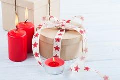 El regalo en la caja de Kraft con el rojo protagoniza la cinta, encendido las velas y corazón Imagen de archivo
