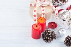 El regalo en la caja de Kraft con el rojo protagoniza la cinta, encendido las velas y decorat Fotos de archivo libres de regalías