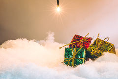 El regalo entre la pila de nieve en la noche silenciosa con una bombilla, enciende para arriba la esperanza y la felicidad en Fel Fotografía de archivo libre de regalías