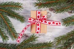El regalo envuelto con la picea del ribbonand ramifica para la Navidad o las tarjetas del día de San Valentín Imagenes de archivo