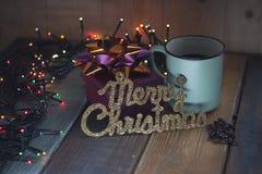 El regalo, la inscripción casa la Navidad y la taza en la tabla Foto de archivo