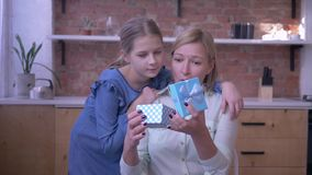 El regalo a la mamá, niña da a la actual madre para el día de fiesta y abraza suavemente en casa y momia sorprendida almacen de metraje de vídeo