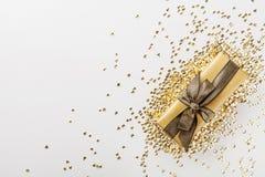 El regalo o la actual caja adornó lentejuelas de oro en la opinión de sobremesa Composición plana de la endecha para la Navidad o Fotos de archivo libres de regalías