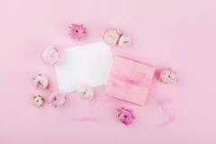 El regalo o la actual caja, el espacio en blanco del Libro Blanco y la primavera florecen en el escritorio rosado desde arriba pa fotos de archivo libres de regalías