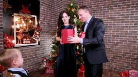 El regalo para los padres, niño felicita a la madre y engendra un día de fiesta feliz, ` s Eve, fiesta de Navidad del Año Nuevo d almacen de video